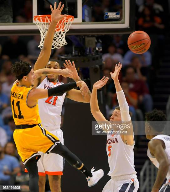 UMBC guard KJ Maura left pass off in the lane against Virginia forward Isaiah Wilkins center and Virginia guard Kyle Guy during the first half in a...