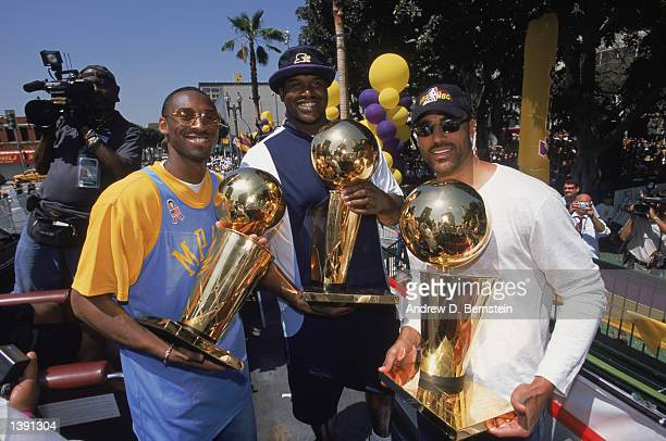 Guard Kobe Bryant center Shaquille O'Neal and forward Rick Fox of the Los Angeles Lakers hold up the their three championship trophies during the...