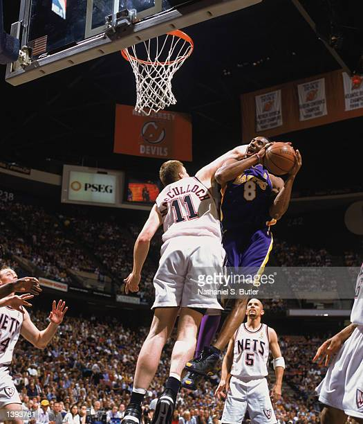 Guard Kobe Bryant of the Los Angeles Lakers batters his way to the rim past center Todd MacCulloch of the New Jersey Nets during Game Four of the...