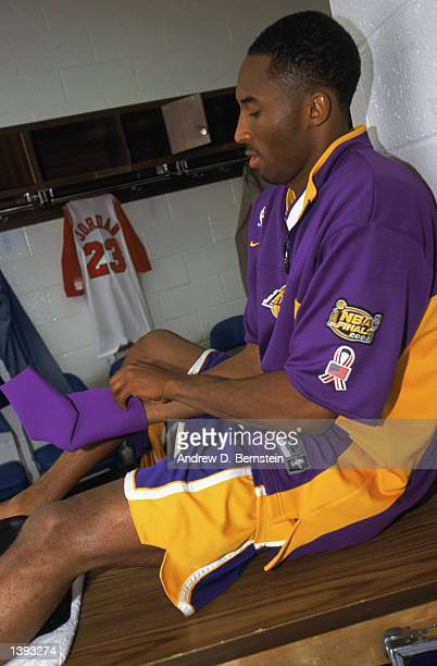 Guard Kobe Bryant of the Los Angeles Lakers dresses in the locker room before Game Four of the 2002 NBA Finals against the New Jersey Nets at...