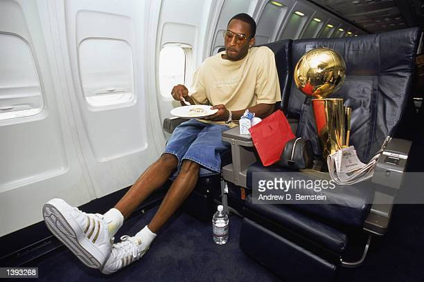Guard Kobe Bryant of the Los Angeles Lakers eats an inflight meal with the championship trophy beside him after Game Four of the 2002 NBA Finals...