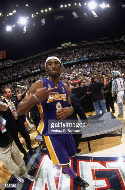 Guard Kobe Bryant of the Los Angeles Lakers gestures in reference to winning three championships in a row after winning Game Four of the 2002 NBA...