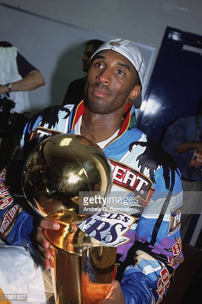 Guard Kobe Bryant of the Los Angeles Lakers holds the championship trophy in the locker room after winning Game Four of the 2002 NBA Finals against...