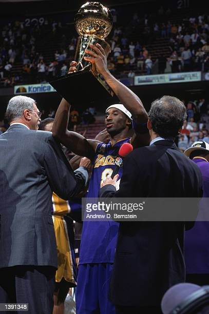 Guard Kobe Bryant of the Los Angeles Lakers holds the championship trophy aloft after winning Game Four of the 2002 NBA Finals against the New Jersey...