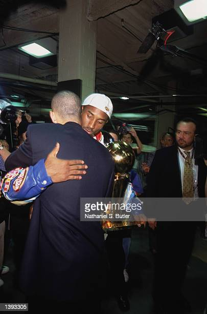 Guard Kobe Bryant of the Los Angeles Lakers holds the championship trophy as he hugs point guard Jason Kidd of the New Jersey Nets after Game Four of...