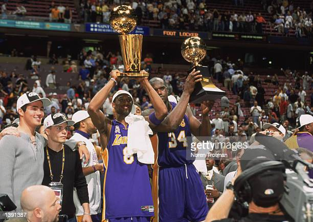 Guard Kobe Bryant of the Los Angeles Lakers holds up the championship trophy as center Shaquille O'Neal holds up his Finals Series MVP trophy after...