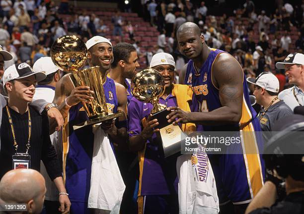 Guard Kobe Bryant of the Los Angeles Lakers holds up the championship trophy as center Shaquille O'Neal hands his Finals Series MVP trophy to guard...