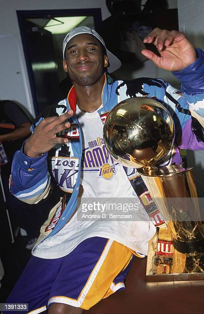 Guard Kobe Bryant of the Los Angeles Lakers holds up three fingers as he poses with the championship trophy in the locker room after winning Game...
