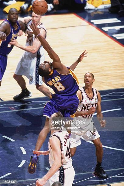 Guard Kobe Bryant of the Los Angeles Lakers leaps for a rebound between forward Keith Van Horn and guard Kerry Kittles of the New Jersey Nets during...