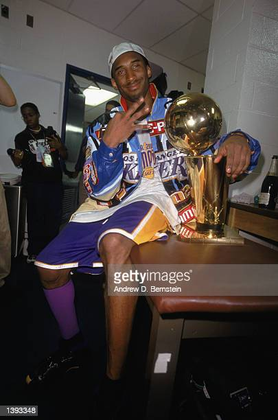 Guard Kobe Bryant of the Los Angeles Lakers sits with the trophy in the locker room as he gestures in reference to winning three championships in a...