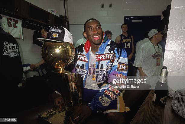 Guard Kobe Bryant of the Los Angeles Lakers sits with the championship trophy in the locker room after winning Game Four of the 2002 NBA Finals...