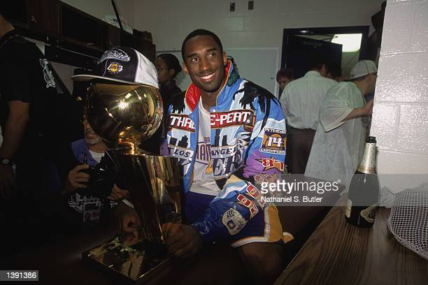 Guard Kobe Bryant of the Los Angeles Lakers smiles as he holds the championship trophy in the locker room after winning Game Four of the 2002 NBA...