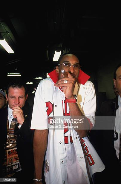 Guard Kobe Bryant of the Los Angeles Lakers smokes a celebratory cigar after winning Game Four of the 2002 NBA Finals against the New Jersey Nets at...