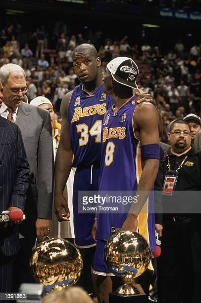 Guard Kobe Bryant of the Los Angeles Lakers stands with center Shaquille O'Neal and head coach Phil Jackson in front of the championship trophy after...