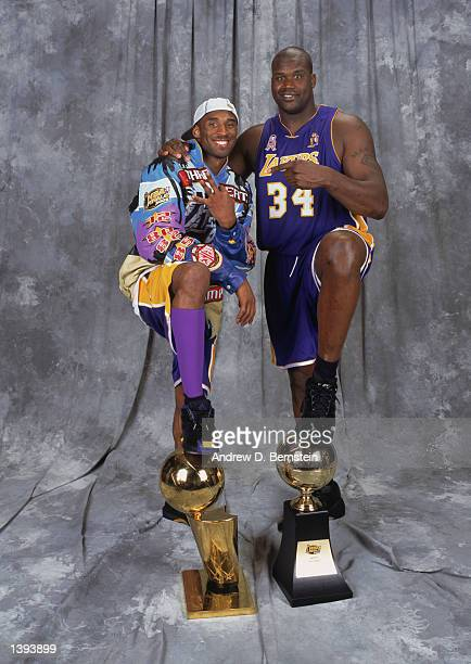 Guard Kobe Bryant of the Los Angeles Lakers stands with center Shaquille O'Neal with the championship and MVP trophies after winning Game Four of the...