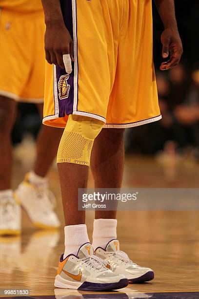 Guard Kobe Bryant of the Los Angeles Lakers stands with his finger wrapped and knee in a brace during the game against the Phoenix Suns in Game One...