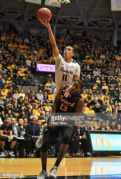 Guard Landry Shamet of the Wichita State Shockers drives to the basket over guard Barry Ogalue of the Long Beach State 49ers during the first half on...