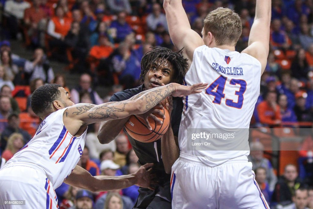 Guard Lindsey Drew #14 of the Nevada Wolf Pack splits the defense of guard Lexus Williams #2 and forward Chris Sengfelder #43 of the Boise State Broncos during first-half action on February 14, 2018 at Taco Bell Arena in Boise, Idaho.