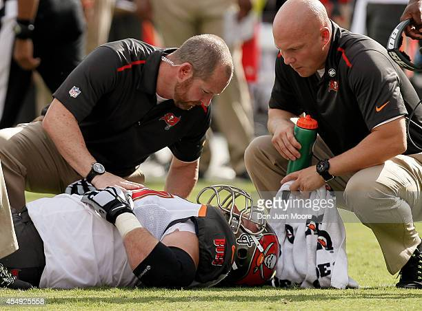 September 7: Guard Logan Mankins of the Tampa Bay Buccaneers is attended by the medical staff of the Buccaneers during the game against the Carolina...