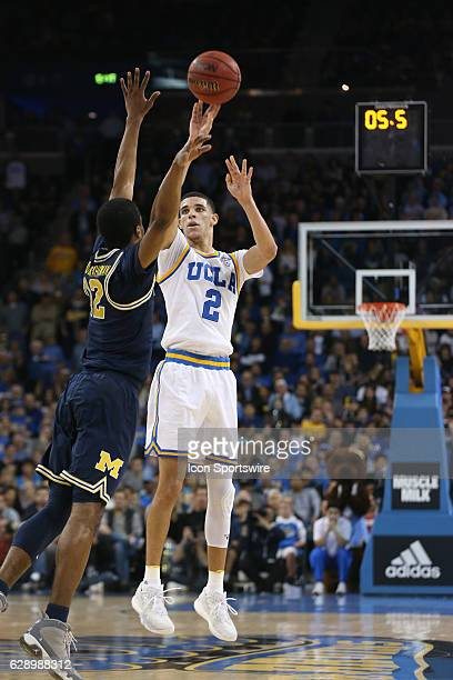 Guard Lonzo Ball makes a three pointer over Michigan guard Duncan Robinson during the game December 10 at the Pauley Pavilion in Los Angeles, CA.