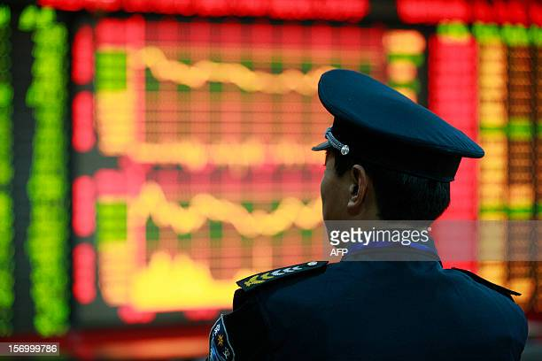 Guard looks around at a securities exchange in Huaibei, central China's Anhui province. Chinese shares closed at their lowest level in nearly four...