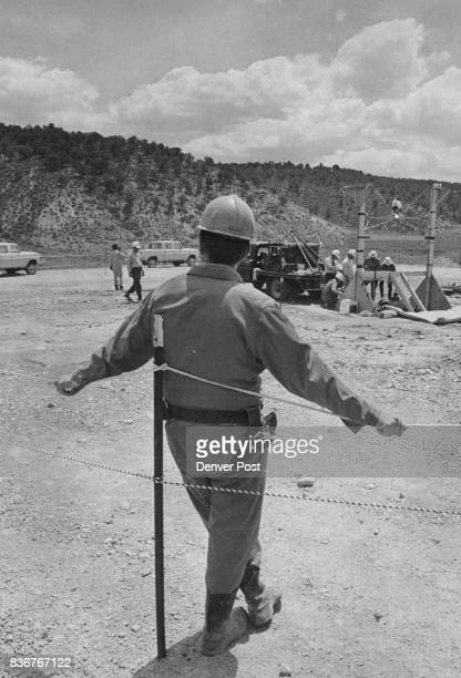 A guard looks on at ground zero as workmen examine the wellhead for effects from the explosion The blast was located a mile underground Credit Denver...