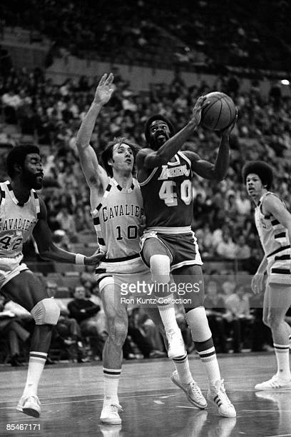 Guard Lucius Allen of the Los Angeles Lakers drives towards the basket as guard Dick Snyder Dwight Davis of the Cleveland Cavaliers during a game on...