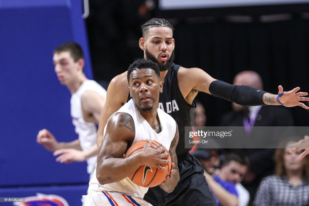 Guard Marcus Dickinson #0 of the Boise State Broncos looks for help against the defense of forward Cody Martin #11 of the Nevada Wolf Pack during first-half action on February 14, 2018 at Taco Bell Arena in Boise, Idaho.