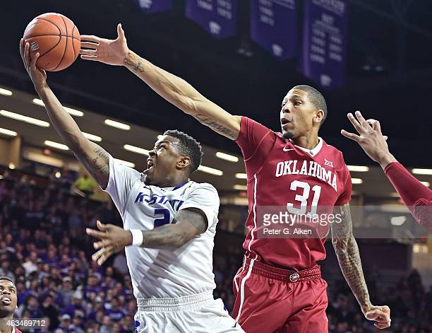 Guard Marcus Foster of the Kansas State Wildcats drives to the basket past forward DJ Bennett of the Oklahoma Sooners during the second half on...