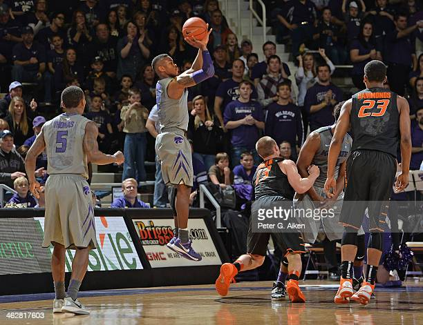 Guard Marcus Foster of the Kansas State Wildcats shoots a threepoint shot over guard Phil Forte of the Oklahoma State Cowboys during the first half...