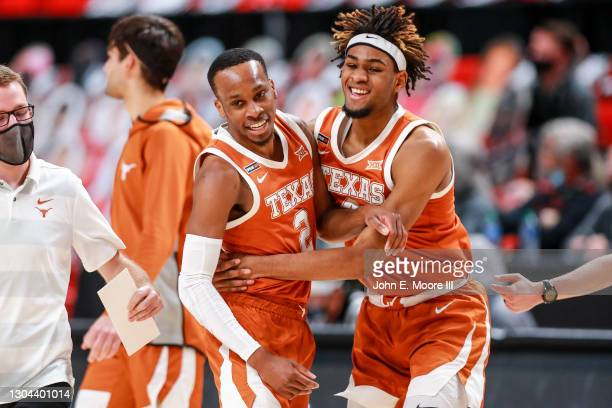 Guard Matt Coleman III of the Texas Longhorns is embraced by forward Greg Brown after making a late three-pointer to end the first half of the...