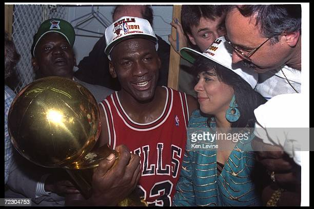 Guard Michael Jordan of the Chicago Bulls celebrates with his wife and the NBA trophy after the Bulls won the NBA championship