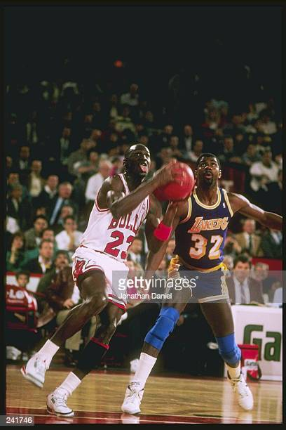 Guard Michael Jordan of the Chicago Bulls drives past Magic Johnson of the Los Angeles Lakers during a game at Chicago Stadium in Chicago Illinios