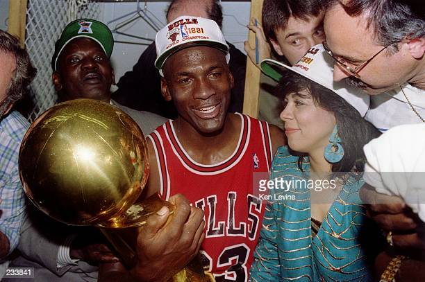 Guard Michael Jordan of the Chicago Bulls sits nexts to his wife Juanita and his dad James while holding the NBA Championship Trophy after the Bulls...