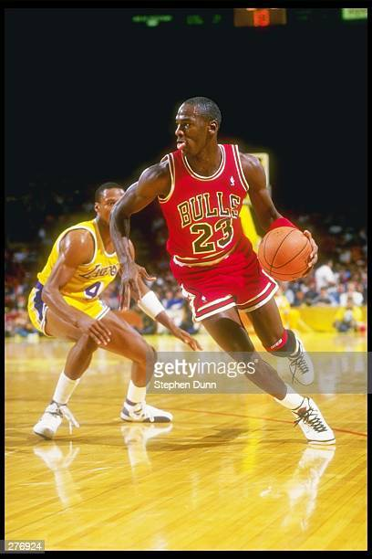 Guard Michael Jordan of the Chicago Bulls swiftly moves away from guard Byron Scott of the Los Angeles Lakers during a game held at The Forum in...