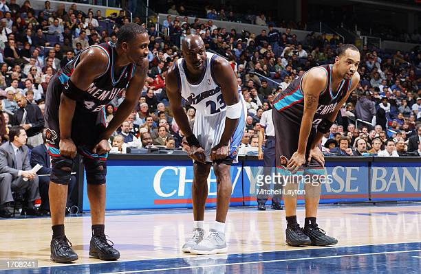 Guard Michael Jordan of the Washington Wizards stands in between center Lorenzen Wright of the Memphis Grizzlies and teammate forward Drew Gooden as...