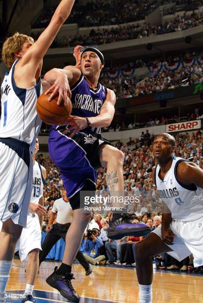 Guard Mike Bibby of the Sacramento Kings throws a behind the back pass while defended by Dirk Nowitzki and Antoine Walker of the Dallas Mavericks in...