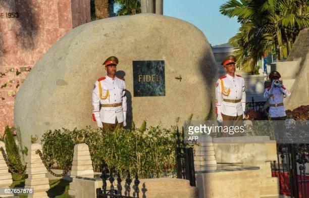 A guard of honour stays by the tomb of Cuban leader Fidel Castro at the Santa Ifigenia cemetery in Santiago de Cuba on December 4 2016 Fidel Castro's...