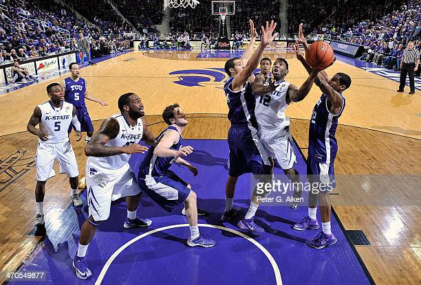 Guard Omari Lawrence of the Kansas State Wildcats drives to the basket between defenders Amric Fields and Jarvis Ray of the TCU Horned Frogs during...