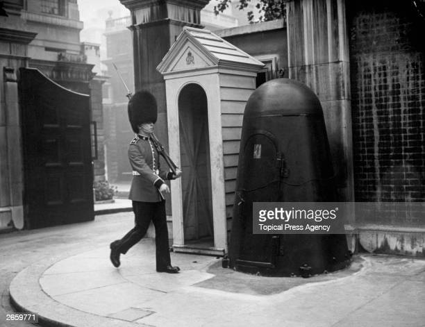 A guard on duty outside Marlborough House London with his individual air raid shelter next to the sentry box