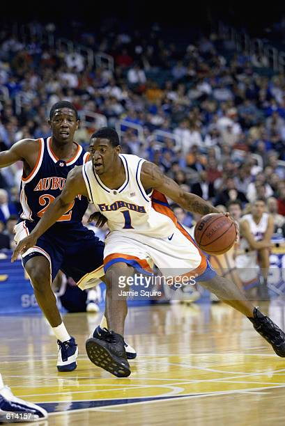 Guard Orien Greene of the Florida Gators drives to the basket against the defense of guard Lewis Monroe of the Auburn Tigers during the first round...