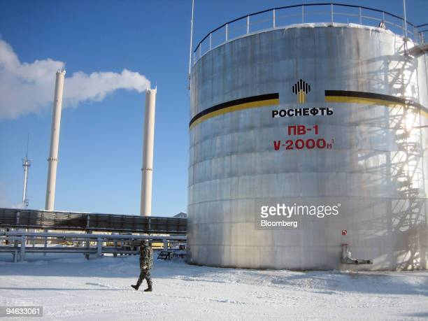 A guard passes an oil storage tank at OAO Rosneft's Priobskoye oil field in western Siberia Russia Tuesday February 20 2007 OOO Yuganskneftegaz which...