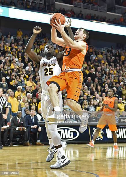 Guard Phil Forte III of the Oklahoma State Cowboys drives to the basket against forward Eric Hamilton of the Wichita State Shockers during the first...