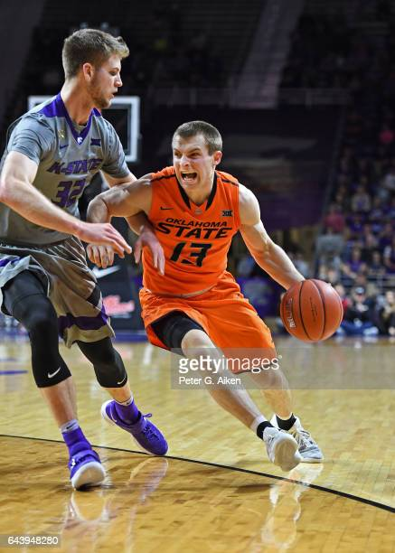 Guard Phil Forte III of the Oklahoma State Cowboys drives to the basket against forward Dean Wade of the Kansas State Wildcats during the first half...