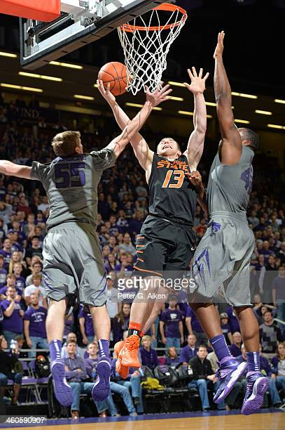 Guard Phil Forte of the Oklahoma State Cowboys drives to the basket against defenders Will Spradling and Thomas Gipson of the Kansas State Wildcats...