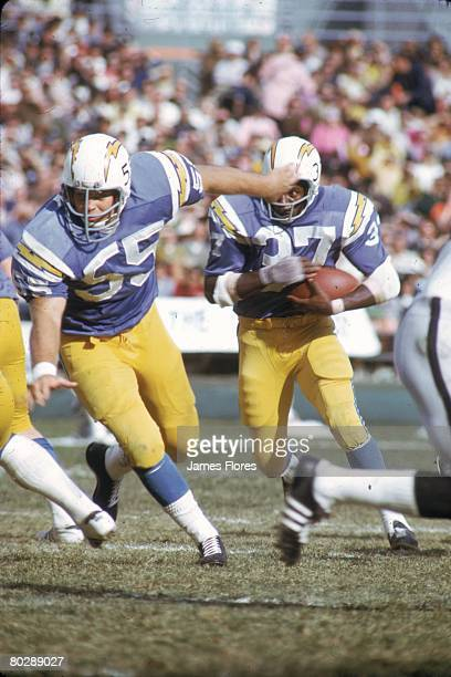 Guard Ralph Wenzel of the San Diego Chargers leads running back Cid Edwards against the Oakland Raiders at San Diego Stadium on December 3 1972 in...
