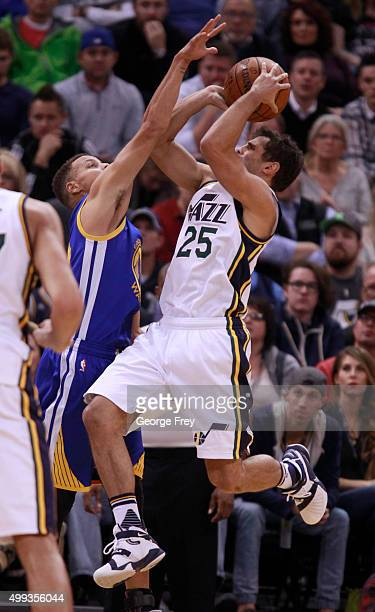 Guard Raul Neto of the Utah Jazz tries to shoot over guard Stephen Curry of the Golden State Warriors during the first half of an NBA game November...