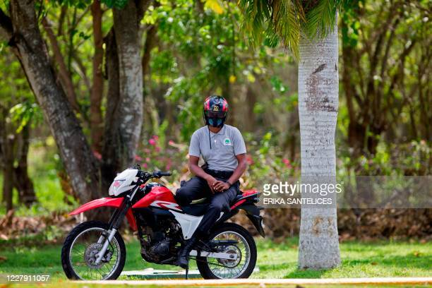 Guard remains with his motorcycle near the entrance to the resort Casa de Campo in La Romana, Dominican Republic, on August 4 where Spain's former...