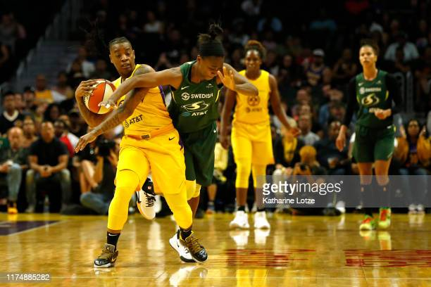 Guard Riquna Williams of the Los Angeles Sparks and guard Jewell Loyd of the Seattle Storm fight for a jump ball during the second half of Seattle...