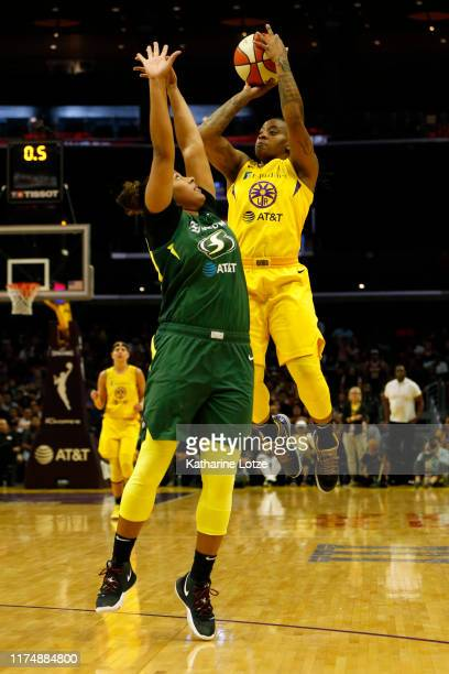 Guard Riquna Williams of the Los Angeles Sparks goes up for a buzzerbeating threepointer as forward Kaleena MosquedaLewis of the Seattle Storm...